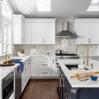 Enclosed kitchen - mid-sized transitional l-shaped brown floor and dark wood floor enclosed kitchen idea in New York with shaker cabinets, white cabinets, quartzite countertops, gray backsplash, marble backsplash, stainless steel appliances, an island, white countertops and an undermount sink