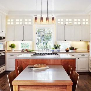 Transitional eat-in kitchen photos - Example of a transitional dark wood floor eat-in kitchen design in San Francisco with raised-panel cabinets, white cabinets, yellow backsplash, stainless steel appliances and an island