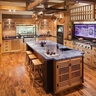 Ispirazione per una grande cucina ad U etnica chiusa con ante in legno scuro, top in granito, isola, lavello sottopiano, elettrodomestici neri e pavimento in legno massello medio