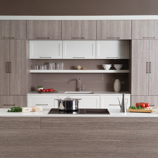 Small contemporary kitchen photos - Example of a small trendy galley slate floor kitchen design in Seattle with an undermount sink, flat-panel cabinets, gray cabinets, gray backsplash, glass sheet backsplash, stainless steel appliances and an island