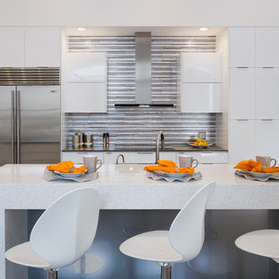 Mid-sized contemporary open concept kitchen designs - Inspiration for a mid-sized contemporary open concept kitchen remodel in Miami with flat-panel cabinets, white cabinets, metallic backsplash, matchstick tile backsplash, stainless steel appliances and an island