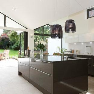 バークシャーの巨大なコンテンポラリースタイルのおしゃれなキッチン (ライムストーンの床、アンダーカウンターシンク、フラットパネル扉のキャビネット、黒いキャビネット、白いキッチンパネル) の写真