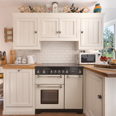 Inspiration for a small timeless l-shaped medium tone wood floor kitchen remodel in Devon with recessed-panel cabinets, white cabinets, wood countertops, white backsplash, white appliances, a peninsula and subway tile backsplash