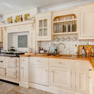 Große Landhaus Wohnküche in L-Form mit Unterbauwaschbecken, Schrankfronten mit vertiefter Füllung, Schränken im Used-Look, Arbeitsplatte aus Holz, Küchenrückwand in Weiß, Keramikboden, Kücheninsel und weißen Elektrogeräten in Devon