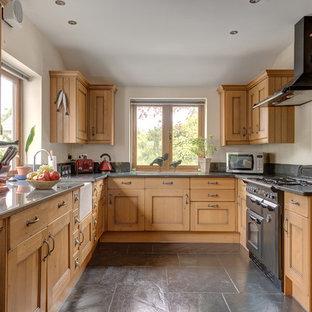 Mittelgroße Landhaus Küche ohne Insel in U-Form mit Schrankfronten mit vertiefter Füllung, hellbraunen Holzschränken, Granit-Arbeitsplatte, schwarzen Elektrogeräten, Landhausspüle und grauem Boden in Devon