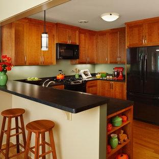 Foto di una cucina american style di medie dimensioni con ante in legno scuro, elettrodomestici neri, pavimento in legno massello medio, ante in stile shaker, penisola, pavimento beige, top nero e top in laminato
