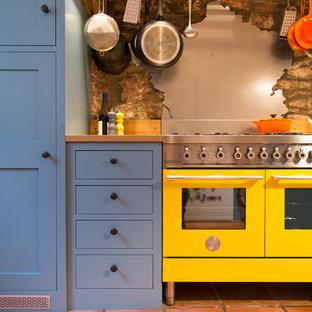 Ejemplo de cocina de galera, contemporánea, pequeña, cerrada, con fregadero sobremueble, armarios estilo shaker, puertas de armario azules, encimera de madera, salpicadero metalizado, salpicadero de metal, electrodomésticos de colores, una isla y suelo de baldosas de terracota