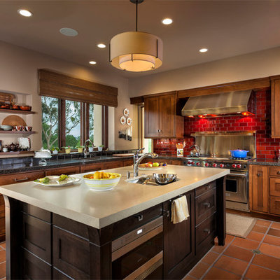 Inspiration for a transitional l-shaped kitchen remodel in Orange County with an undermount sink, shaker cabinets, dark wood cabinets, red backsplash, subway tile backsplash and stainless steel appliances