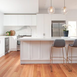 Large transitional l-shaped open plan kitchen in Melbourne with an undermount sink, white cabinets, white splashback, stone slab splashback, stainless steel appliances, medium hardwood floors, with island, white benchtop, shaker cabinets and beige floor.