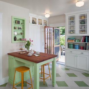 Mid-sized traditional l-shaped eat-in kitchen in San Diego with recessed-panel cabinets, white cabinets, green splashback, glass tile splashback, a farmhouse sink, solid surface benchtops, stainless steel appliances, green floor and linoleum floors.
