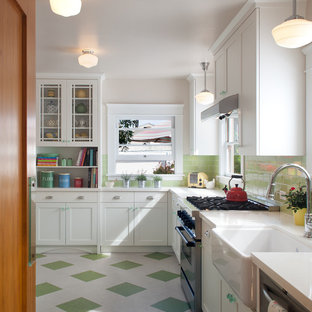 Photo of a mid-sized traditional l-shaped eat-in kitchen in San Diego with a farmhouse sink, recessed-panel cabinets, white cabinets, solid surface benchtops, green splashback, glass tile splashback, stainless steel appliances, linoleum floors, no island, green floor and white benchtop.
