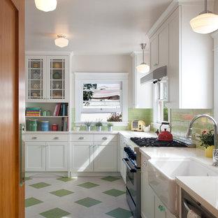Exemple d'une cuisine américaine chic en L de taille moyenne avec un évier de ferme, un placard avec porte à panneau encastré, des portes de placard blanches, un plan de travail en surface solide, une crédence verte, une crédence en carreau de verre, un électroménager en acier inoxydable, un sol en linoléum, aucun îlot, un sol vert et un plan de travail blanc.
