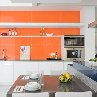 Immagine di una cucina minimal con lavello sottopiano, ante lisce, ante bianche, elettrodomestici in acciaio inossidabile e isola