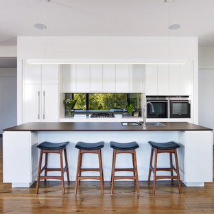Inspiration for a large contemporary galley kitchen in Other with flat-panel cabinets, white cabinets, solid surface benchtops, metallic splashback, mirror splashback, black appliances, medium hardwood floors, with island, brown floor, brown benchtop and a drop-in sink.