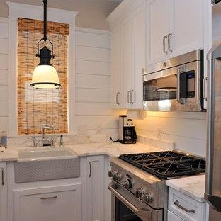 Modelo de cocina en L, costera, pequeña, cerrada, sin isla, con fregadero sobremueble, armarios estilo shaker, puertas de armario blancas, encimera de mármol y electrodomésticos de acero inoxidable