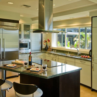 Inspiration for a contemporary l-shaped kitchen in Hawaii with flat-panel cabinets, stainless steel appliances, granite benchtops, a double-bowl sink, green splashback and green benchtop.