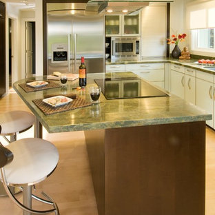 Inspiration for a contemporary l-shaped eat-in kitchen remodel in Hawaii with glass-front cabinets, stainless steel appliances, an undermount sink, granite countertops, green backsplash and green countertops