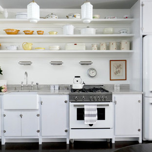 Idéer för ett litet nordiskt linjärt kök och matrum, med en rustik diskho, släta luckor, vita skåp, vita vitvaror, bänkskiva i kvartsit, vitt stänkskydd, korkgolv och brunt golv