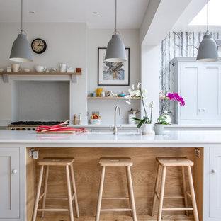 Große Skandinavische Wohnküche in L-Form mit Kücheninsel, Landhausspüle, Schrankfronten im Shaker-Stil, weißen Schränken, Quarzwerkstein-Arbeitsplatte und bunten Elektrogeräten in Sonstige