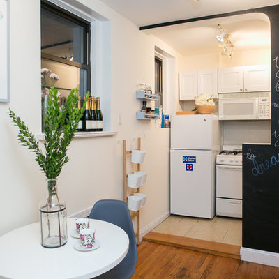 Small cottage chic single-wall medium tone wood floor eat-in kitchen photo in New York with white cabinets