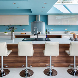 Photo of a contemporary l-shaped kitchen in Manchester with a built-in sink, flat-panel cabinets, white cabinets, blue splashback, an island, white floors and white worktops.