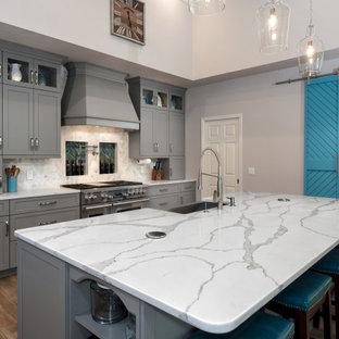 Idéer för stora vintage vitt kök, med en rustik diskho, skåp i shakerstil, grå skåp, bänkskiva i kvarts, grått stänkskydd, glaspanel som stänkskydd, rostfria vitvaror, klinkergolv i keramik, en köksö och brunt golv