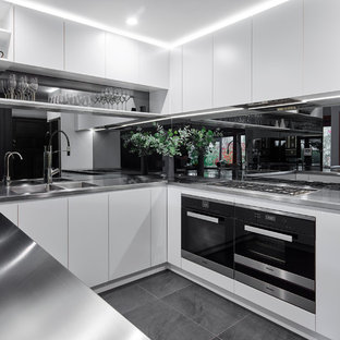 Inspiration for a large contemporary u-shaped eat-in kitchen in Adelaide with an integrated sink, white cabinets, stainless steel benchtops, glass sheet splashback, stainless steel appliances, ceramic floors and a peninsula.