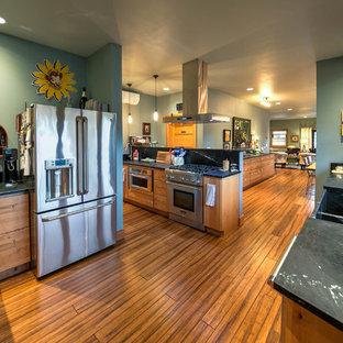 Bild på ett mellanstort amerikanskt kök, med en rustik diskho, släta luckor, skåp i ljust trä, bänkskiva i täljsten, svart stänkskydd, stänkskydd i sten, rostfria vitvaror, bambugolv och brunt golv