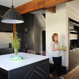 バンクーバーの中サイズのエクレクティックスタイルのおしゃれなキッチン (エプロンフロントシンク、フラットパネル扉のキャビネット、黒いキャビネット、クオーツストーンカウンター、白いキッチンパネル、セラミックタイルのキッチンパネル、シルバーの調理設備の、無垢フローリング) の写真