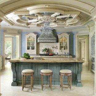 Foto på ett stort vintage kök, med en rustik diskho, luckor med profilerade fronter, beige skåp, bänkskiva i kalksten, beige stänkskydd, stänkskydd i mosaik, svarta vitvaror, kalkstensgolv och flera köksöar