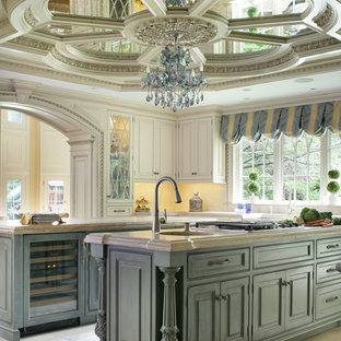 This is an example of a large traditional u-shaped eat-in kitchen in New York with a farmhouse sink, beaded inset cabinets, beige cabinets, limestone benchtops, beige splashback, mosaic tile splashback, coloured appliances, limestone floors and multiple islands.