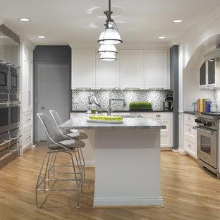 На фото: кухни в современном стиле с техникой из нержавеющей стали, обеденным столом, раковиной в стиле кантри, фасадами в стиле шейкер, белыми фасадами, столешницей из кварцевого композита, светлым паркетным полом и островом