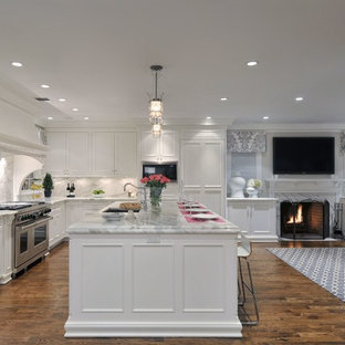 Photo of a large classic l-shaped open plan kitchen in New York with white cabinets, white splashback, integrated appliances, an island, recessed-panel cabinets, marble worktops, stone slab splashback, a submerged sink and dark hardwood flooring.