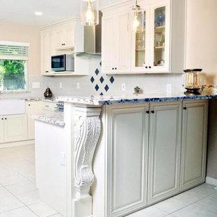 Inspiration för mellanstora klassiska svart kök, med en rustik diskho, luckor med upphöjd panel, vita skåp, kaklad bänkskiva, vitt stänkskydd, stänkskydd i porslinskakel, svarta vitvaror, klinkergolv i porslin, en halv köksö och vitt golv