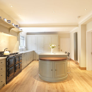 Photo of a large traditional u-shaped kitchen/diner in Hampshire with shaker cabinets, beige cabinets, engineered stone countertops, beige splashback, ceramic splashback, black appliances, light hardwood flooring and an island.