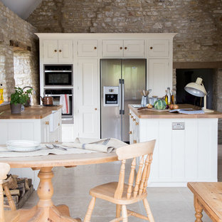 Inspiration for a medium sized country l-shaped open plan kitchen in Other with a belfast sink, white cabinets, wood worktops, ceramic flooring, an island, stainless steel appliances and beaded cabinets.