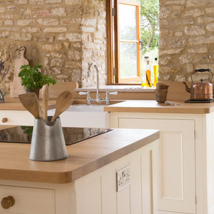 This is an example of a large rural l-shaped open plan kitchen in Other with a belfast sink, white cabinets, wood worktops, ceramic flooring, an island, stainless steel appliances and beaded cabinets.