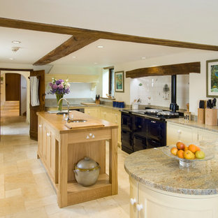 Design ideas for a country u-shaped kitchen in Hampshire with a submerged sink, shaker cabinets, yellow cabinets, white splashback, ceramic splashback, limestone flooring, an island and black appliances.