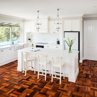 This is an example of a large traditional l-shaped eat-in kitchen in Melbourne with shaker cabinets, with island, a farmhouse sink, white cabinets, quartz benchtops, black appliances and dark hardwood floors.
