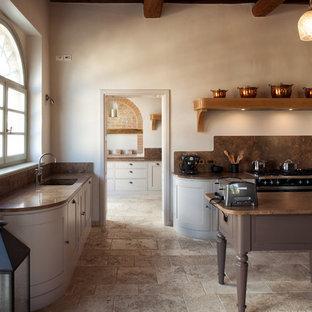 Cette image montre une cuisine ouverte rustique en L avec un évier encastré, un placard à porte affleurante, des portes de placard grises, un plan de travail en marbre, une crédence marron, une crédence en dalle de pierre, un électroménager noir, un sol en calcaire et un îlot central.