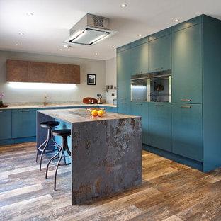他の地域の中くらいのコンテンポラリースタイルのおしゃれなキッチン (ドロップインシンク、フラットパネル扉のキャビネット、緑のキャビネット、タイルカウンター、グレーのキッチンパネル、木材のキッチンパネル、シルバーの調理設備、ラミネートの床、茶色い床、茶色いキッチンカウンター) の写真
