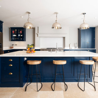 This is an example of a classic l-shaped kitchen in Cardiff with a belfast sink, shaker cabinets, blue cabinets, stainless steel appliances, an island, beige floors and white worktops.
