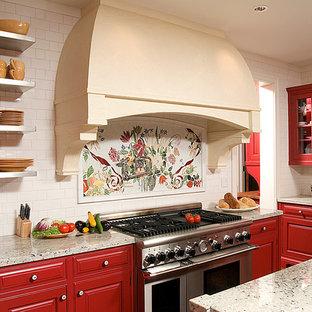 Klassische Küche mit roten Schränken, Granit-Arbeitsplatte, Kücheninsel, Kassettenfronten, bunter Rückwand und Küchengeräten aus Edelstahl in Sonstige
