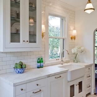 オースティンの小さいトラディショナルスタイルのおしゃれな独立型キッチン (エプロンフロントシンク、落し込みパネル扉のキャビネット、白いキャビネット、大理石カウンター、白いキッチンパネル、サブウェイタイルのキッチンパネル、アイランドなし、磁器タイルの床) の写真