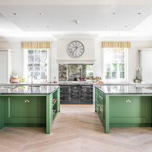 Expansive traditional kitchen in Wiltshire with mirror splashback, light hardwood flooring, multiple islands, a submerged sink, shaker cabinets, grey cabinets, black appliances, beige floors, white worktops and granite worktops.