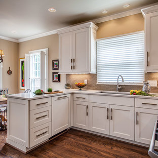 Mid-sized traditional eat-in kitchen designs - Mid-sized elegant u-shaped medium tone wood floor eat-in kitchen photo in Nashville with an undermount sink, recessed-panel cabinets, white cabinets, quartz countertops, gray backsplash, glass tile backsplash, stainless steel appliances and a peninsula