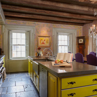 Large eclectic eat-in kitchen pictures - Eat-in kitchen - large eclectic single-wall gray floor eat-in kitchen idea in Boston with a farmhouse sink, raised-panel cabinets, yellow cabinets, concrete countertops, multicolored backsplash, mosaic tile backsplash, stainless steel appliances, an island and gray countertops