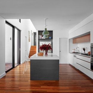 Inspiration for a contemporary l-shaped kitchen in Perth with quartz benchtops, white splashback, with island, flat-panel cabinets, white cabinets, stainless steel appliances, dark hardwood floors, brown floor and white benchtop.