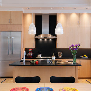 Example of a large trendy u-shaped linoleum floor eat-in kitchen design in DC Metro with an undermount sink, flat-panel cabinets, light wood cabinets, granite countertops, black backsplash, stone slab backsplash, stainless steel appliances and an island