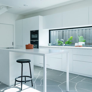 Photo of a mid-sized modern galley open plan kitchen in Perth with white cabinets, concrete benchtops and with island.